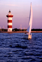 Sailboat on the lake and view of the lighthouse in the background.