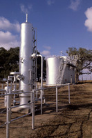 A collection field with new tanks. Gas collection in the foreground with crude oil storage tanks in the background.