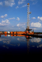 Water storage pond creates a great reflection of the drilling rig.