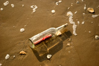 A S.O.S. message in a bottle washed-up with surf on the beach.