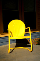 A classic metal chair painted a bright yellow color.