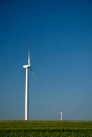 Wind turbine isolated in green field with blue sky.