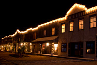 A rustic old west town that is decorated in Christmas lights.