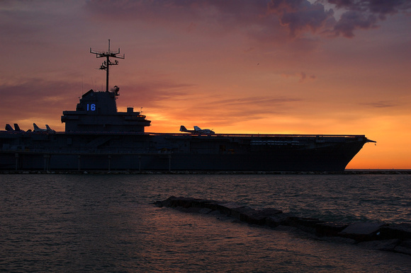 USS Lexington aircraft carrier is silhouetted against morning sunrise.