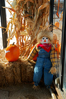 Harvest decoration of pumpkin, scarecrow, hay, and corn stalks.