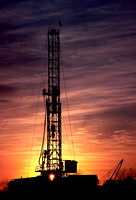 Gas drilling rig silhouetted by the late evening sun.